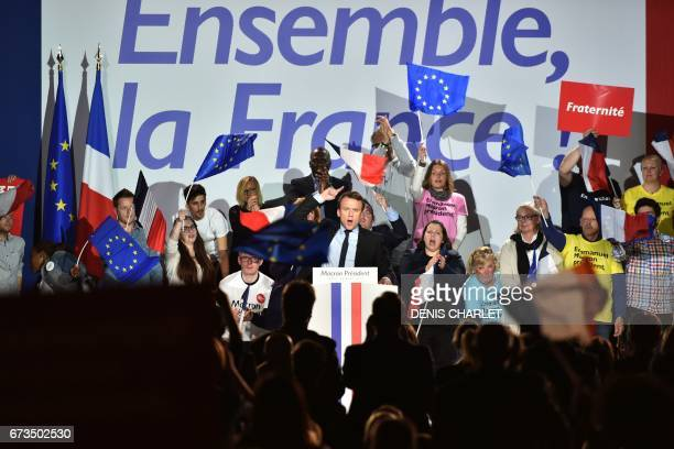 TOPSHOT French presidential election candidate for the En Marche movement Emmanuel Macron gestures as he delivers a speech during a campaign rally in...