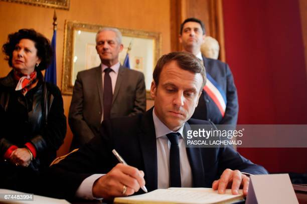 French presidential election candidate for the En Marche movement Emmanuel Macron flanked by Mayor of OradoursurGlane Philippe Lacroix signs the...
