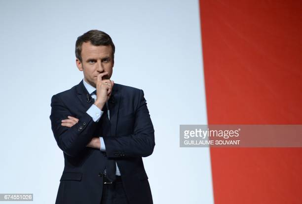 French presidential election candidate for the En Marche movement Emmanuel Macron listens to a militant's question as he gives a speech on April 28...