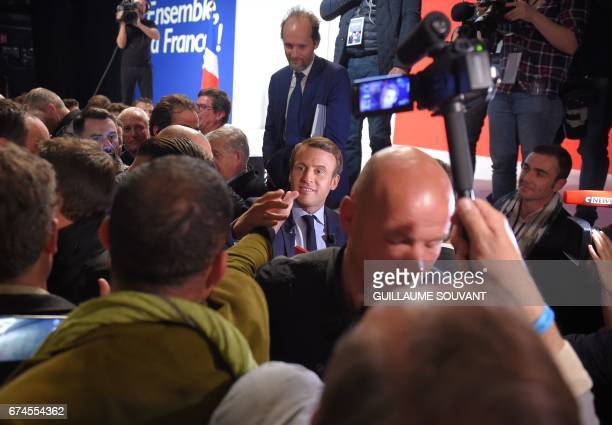 French presidential election candidate for the En Marche movement Emmanuel Macron shakes hands with supporters following his speech ahead of the...