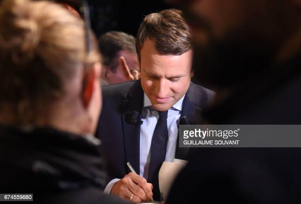 French presidential election candidate for the En Marche movement Emmanuel Macron signs an autograph following his speech ahead of the second and...