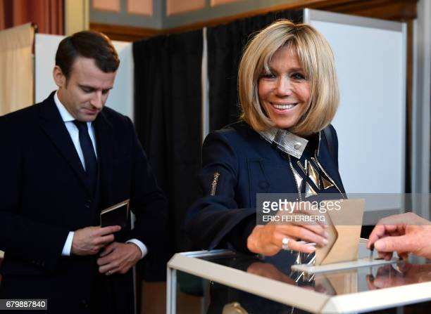 French presidential election candidate for the En Marche movement Emmanuel Macron looks on as his wife Brigitte Trogneux casts her ballot at a...