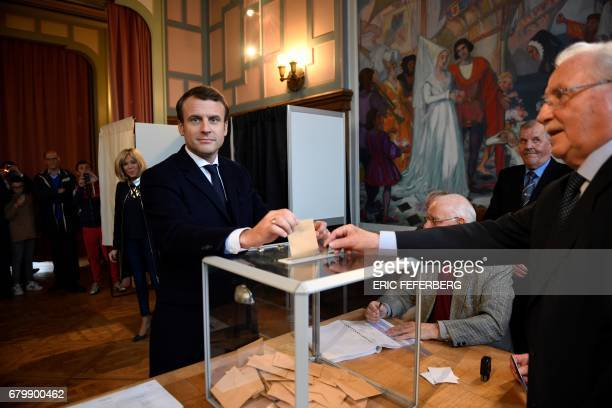 TOPSHOT French presidential election candidate for the En Marche movement Emmanuel Macron casts his ballot at a polling station in Le Touquet...