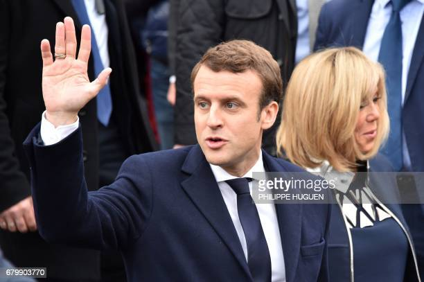 French presidential election candidate for the En Marche movement Emmanuel Macron waves to supporters next to his wife Brigitte Trogneux as they...
