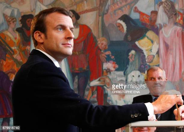 French presidential election candidate for the En Marche movement Emmanuel Macron casts his ballot at a polling station in Le Touquet northern France...
