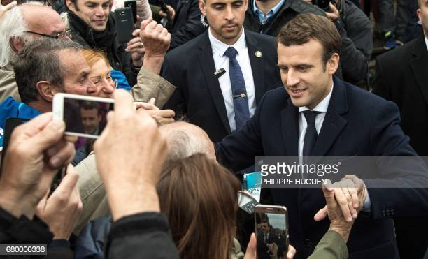French presidential election candidate for the En Marche movement Emmanuel Macron shakes hands with supporters in Le Touquet northern France on May 7...