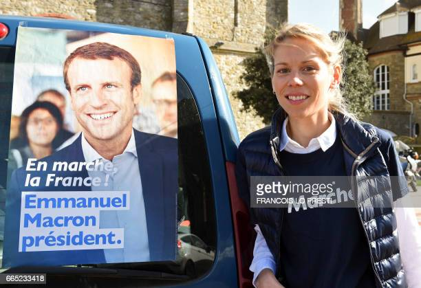 French presidential election candidate for the EnMarche movement Emmanuel Macron's stepdaughter Tiphaine Auzière poses next to an electoral poster of...
