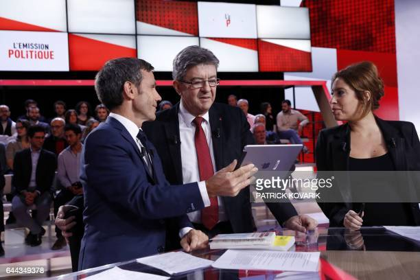 French presidential election candidate for the farleft coalition 'La France insoumise' JeanLuc Melenchon looks at a tablet next to journalists and TV...