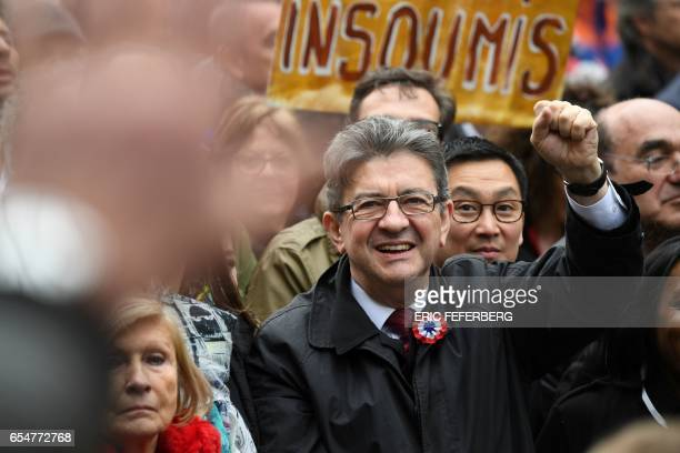 TOPSHOT French presidential election candidate for the farleft coalition 'La France insoumise' JeanLuc Melenchon raises his fist as he takes part in...