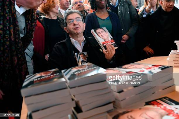 French presidential election candidate for the farleft coalition 'La France insoumise' JeanLuc Melenchon holds copies of his book 'Le choix de...