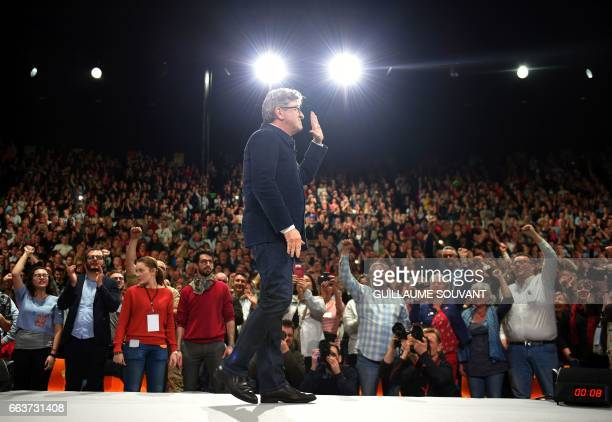 TOPSHOT French presidential election candidate for the farleft coalition La France insoumise JeanLuc Melenchon waves on stage during a campaign rally...