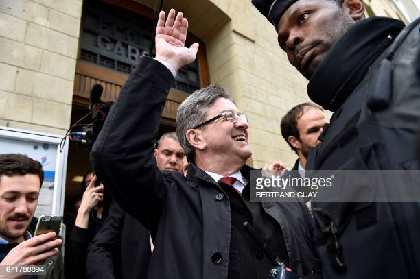 TOPSHOT French presidential election candidate for the farleft coalition La France Insoumise JeanLuc Melenchon waves as he leaves a polling station...