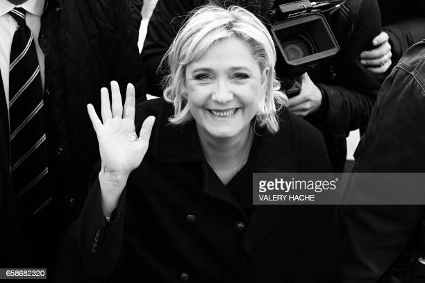 French presidential election candidate for the farright Front National party Marine Le Pen waves as she walks on the beach during her visit in Nice...