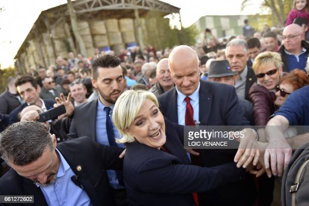TOPSHOT French presidential election candidate for the farright Front National party Marine Le Pen shakes hands with supporters after a campaign...