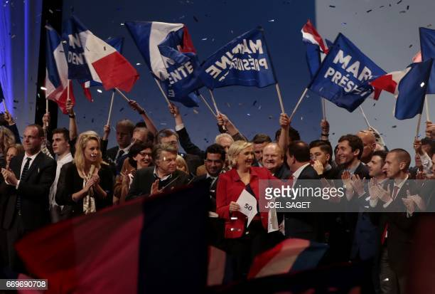 French presidential election candidate for the farright Front National party Marine Le Pen smiles after being handed a piece of paper marked 50% by...