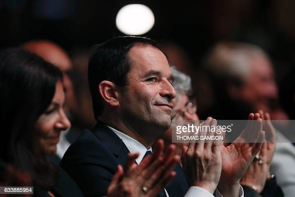 TOPSHOT French presidential election candidate for the leftwing French Socialist party Benoit Hamon applauses next to Paris' mayor Anne Hidalgo...