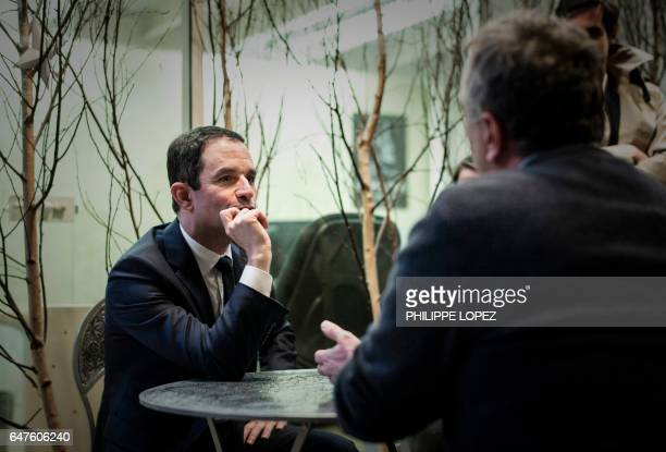 French presidential election candidate for the leftwing French Socialist party Benoit Hamon listens during a visit at 'La Ruche' a coworking space...