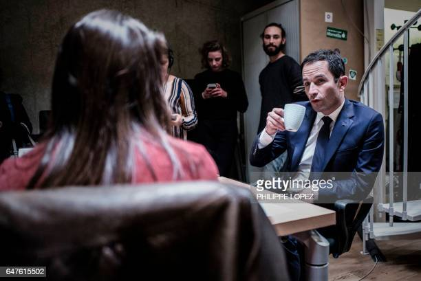 French presidential election candidate for the leftwing French Socialist party Benoit Hamon talks to an entrepreneur during a visit at 'La Ruche' a...