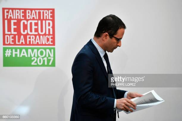 TOPSHOT French presidential election candidate for the leftwing French Socialist party Benoit Hamon looks at documents as he addresses the press on...