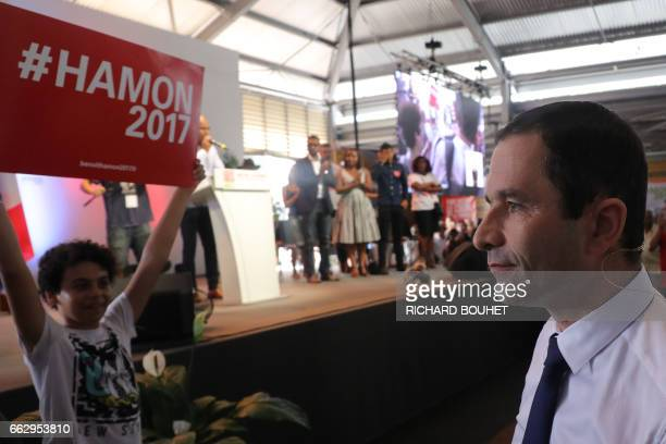French presidential election candidate for the leftwing French Socialist party Benoit Hamon looks on as a child holds a banner in his support in...
