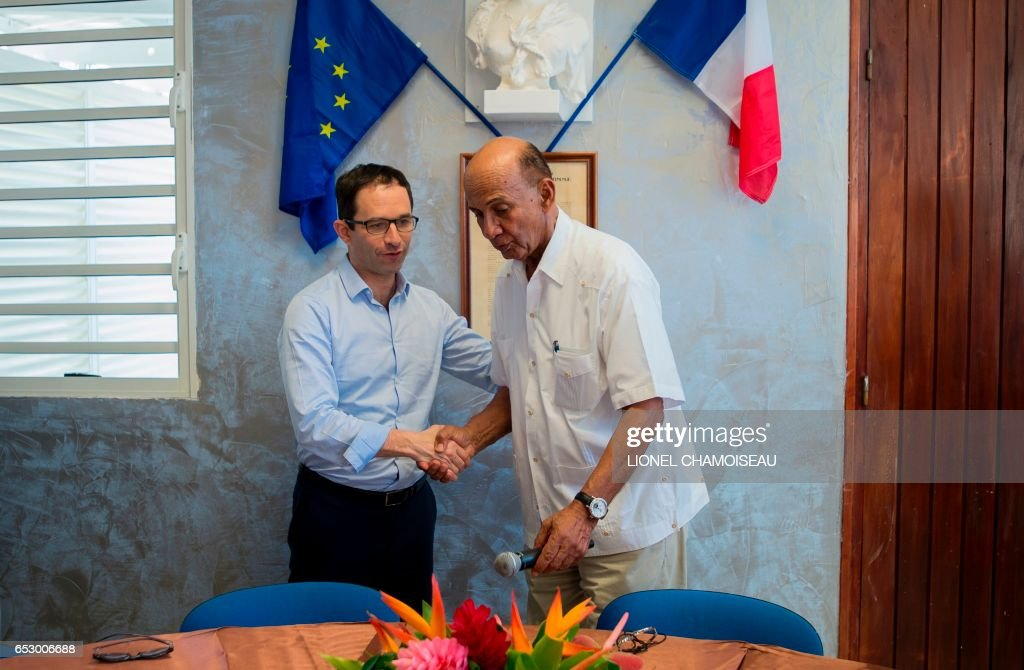 French presidential election candidate for the left-wing Socialist Party (PS) Benoit Hamon (L) shakes hands with Mayor of Le Marin Rodolphe Desire in Le Marin on March 13, 2017, during a trip to the French overseas territory of Martinique. / AFP PHOTO / Lionel CHAMOISEAU