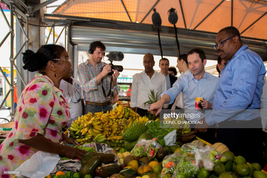 French presidential election candidate for the left-wing Socialist Party (PS) Benoit Hamon (2nd R), National Assembly member Serge Letchimy (C), points to fruit at a stall at the market of Fort-de-France on March 13, 2017, during a trip to the French overseas territory of Martinique. / AFP PHOTO / Lionel CHAMOISEAU