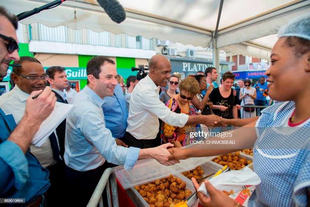 French presidential election candidate for the left-wing Socialist Party (PS) Benoit Hamon (C), flanked by Mayor of Fort-de-France Didier Laguerre (2nd L) and National Assembly member Serge Letchimy (C-R), greets a vendor at the market of Fort-de-France on March 13, 2017, during a trip to the French overseas territory of Martinique. / AFP PHOTO / Lionel CHAMOISEAU