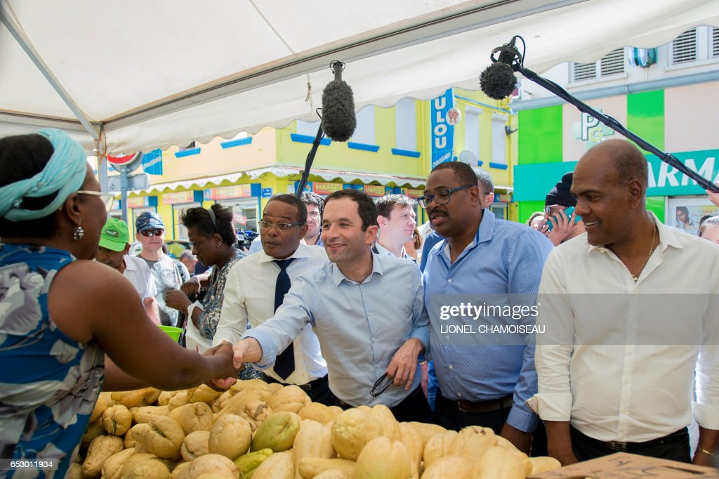 French presidential election candidate for the left-wing Socialist Party (PS) Benoit Hamon (C), flanked by Mayor of Fort-de-France Didier Laguerre (L) and National Assembly member Serge Letchimy (R), greets a vendor at the market of Fort-de-France on March 13, 2017, during a trip to the French overseas territory of Martinique. / AFP PHOTO / Lionel CHAMOISEAU