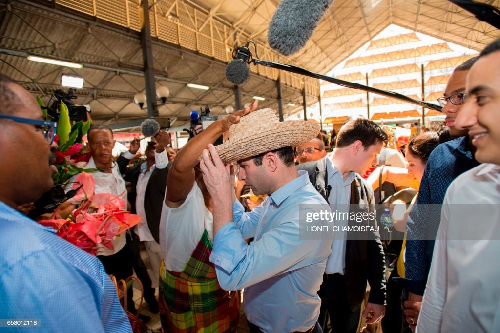 French presidential election candidate for the left-wing Socialist Party (PS) Benoit Hamon (C), tries on a hat at the market of Fort-de-France on March 13, 2017, during a trip to the French overseas territory of Martinique. / AFP PHOTO / Lionel CHAMOISEAU