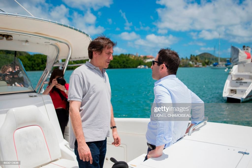 French presidential election candidate for the left-wing Socialist Party (PS) Benoit Hamon (R) speaks to French Socialist Party President of the General Council of Essonne Jerome Guedj on a boat at a dry dock in Le Marin on March 13, 2017, during a trip to the French overseas territory of Martinique. / AFP PHOTO / Lionel CHAMOISEAU
