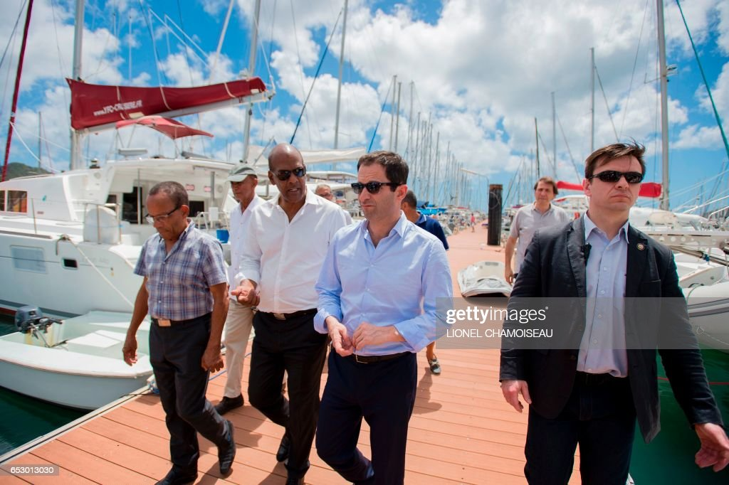 French presidential election candidate for the left-wing Socialist Party (PS) Benoit Hamon (C) speaks to National Assembly member Serge Letchimy (C-L) at a dry dock in Le Marin on March 13, 2017, d...