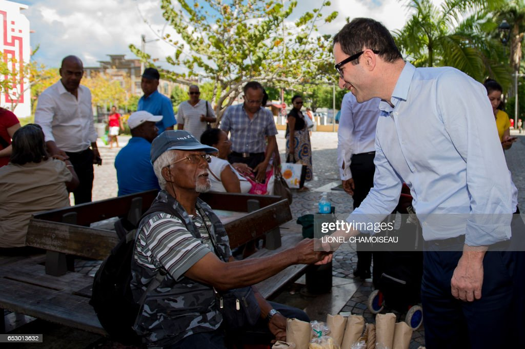 French presidential election candidate for the left-wing Socialist Party (PS) Benoit Hamon (R) shakes hands with a local in Fort-de-France during a visit to the French overseas territory of Martinique on March 13, 2017. / AFP PHOTO / Lionel CHAMOISEAU