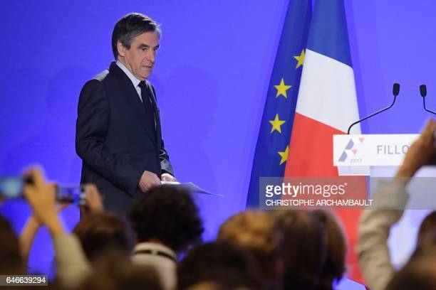 French presidential election candidate for the rightwing Les Republicains party Francois Fillon walks on stage to give a press conference on March 1...