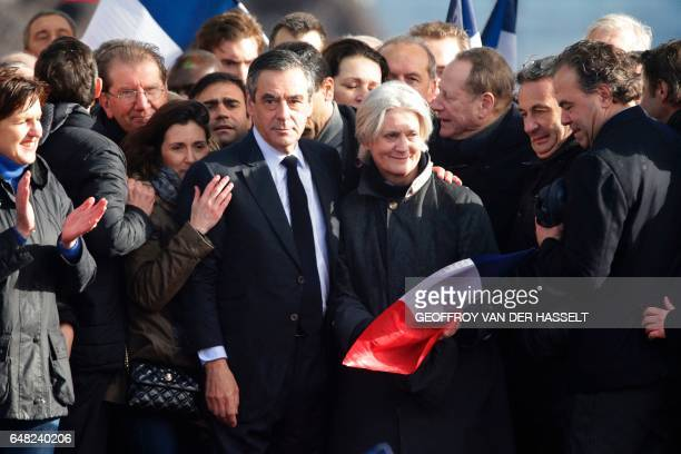 French presidential election candidate for the rightwing Les Republicains party Francois Fillon holds by the shoulder his wife Penelope Fillon and...
