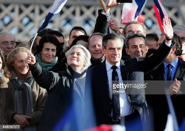 French presidential election candidate for the rightwing 'Les Republicains' party Francois Fillon flanked by his wife Penelope Fillon acknowledges...