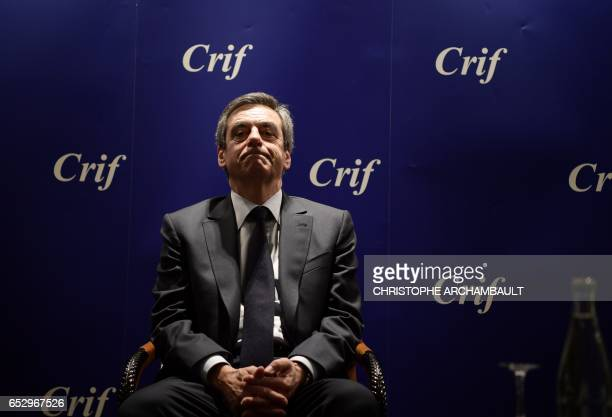 TOPSHOT French presidential election candidate for the rightwing Les Republicains party Francois Fillon looks on as he sits during a conference at...