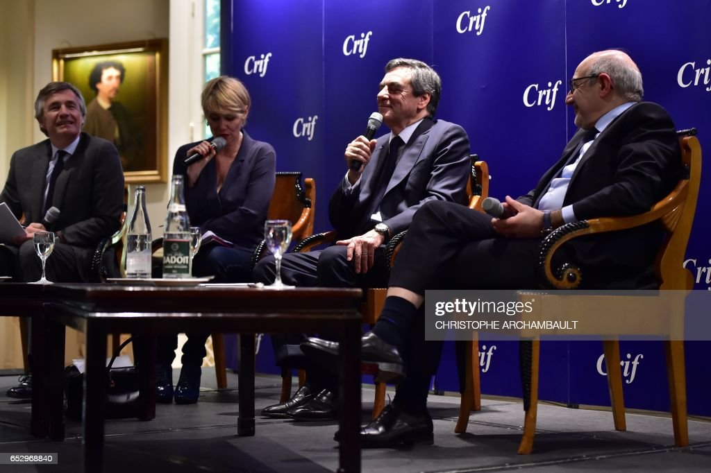 French presidential election candidate for the right-wing Les Republicains (LR) party Francois Fillon (2R), flanked by Francis Kalifat (R) president of the Jewish Institutions Representative Council (Conseil Representatif des Institutions juives de France - CRIF) and TV hosts, speaks during a conference CRIF on March 13, 2017 in Paris. /