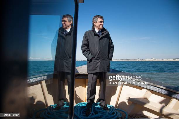 TOPSHOT French presidential election candidate for the rightwing Les Republicains party Francois Fillon stands aboard a fishing boat during a visit...