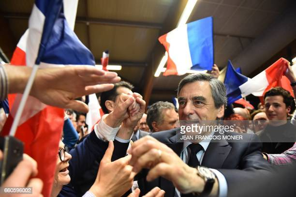 French presidential election candidate for the rightwing Les Republicains party Francois Fillon shakes hands as he arrives to a campaign meeting on...
