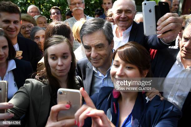 French presidential election candidate for the rightwing Les Republicains party Francois Fillon poses with two supporters for photographs upon his...