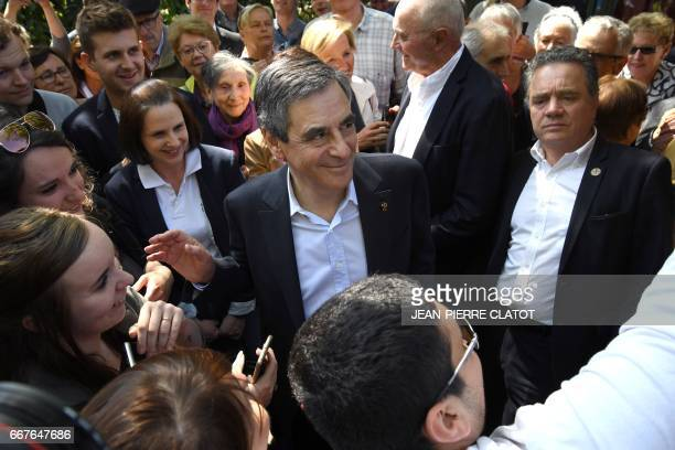 French presidential election candidate for the rightwing Les Republicains party Francois Fillon reacts as he is greeted by supporters upon his...
