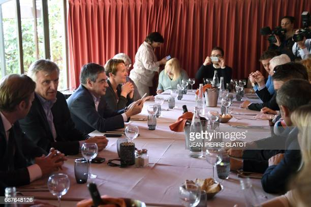 French presidential election candidate for the rightwing Les Republicains party Francois Fillon looks at his mobile phone during a meeting with...