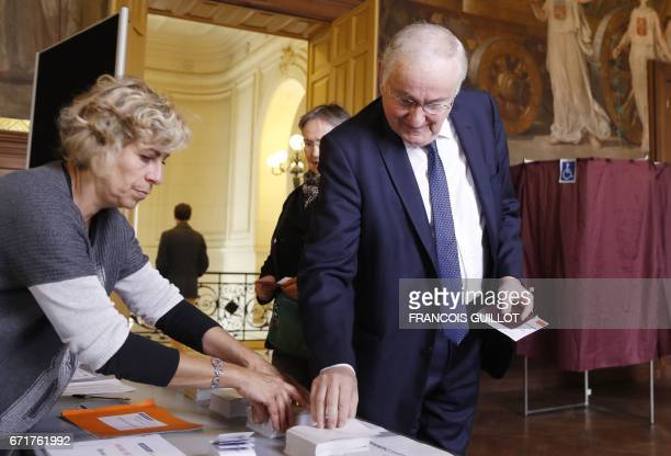 French presidential election candidate for the Solidarite et Progres party Jacques Cheminade picks up ballots before casting his vote at a polling...