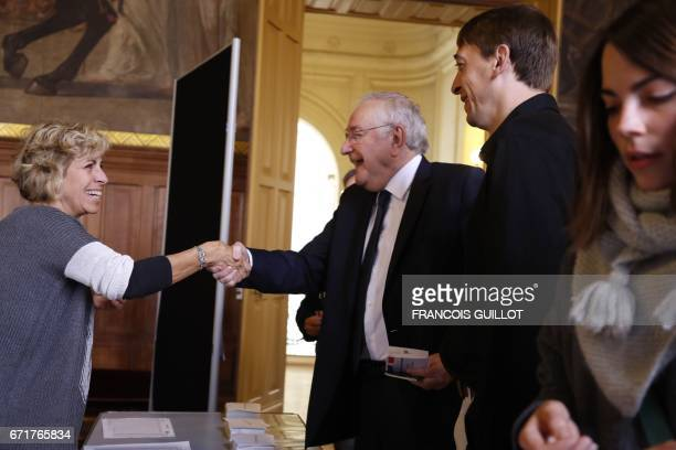 French presidential election candidate for the Solidarite et Progres party Jacques Cheminade shakes hands with a polling official before casting his...