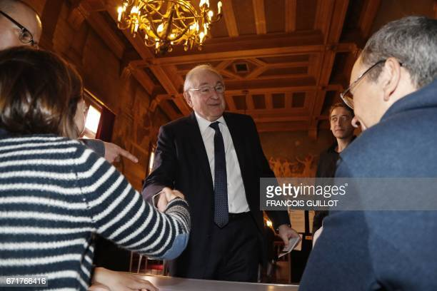 French presidential election candidate for the Solidarite et Progres party Jacques Cheminade shakes hands with polling officials before casting his...