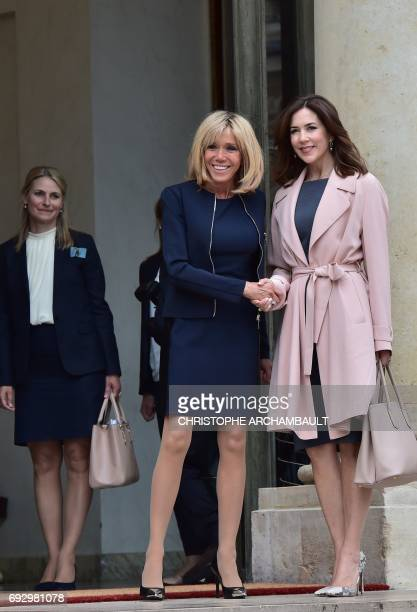 French president's wife Brigitte Macron shakes hands with Princess Mary of Denmark after a meeting on climate change on June 6 2017 at the Elysee...