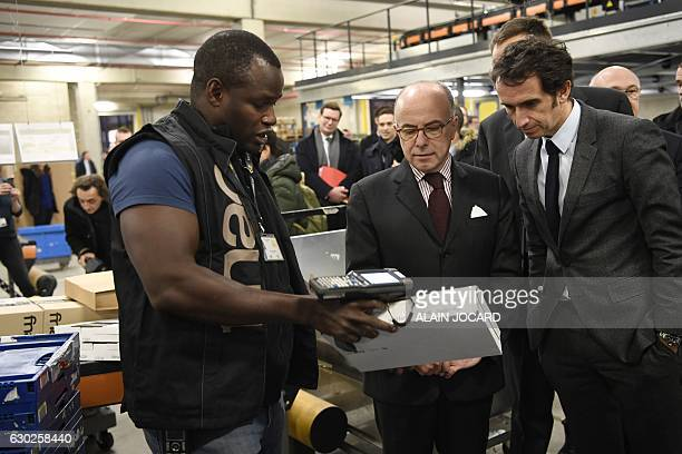 French Prime Minister Bernard Cazeneuve and French retail chain FNAC chairperson Alexandre Bompard listen to an employee during a visit to the...