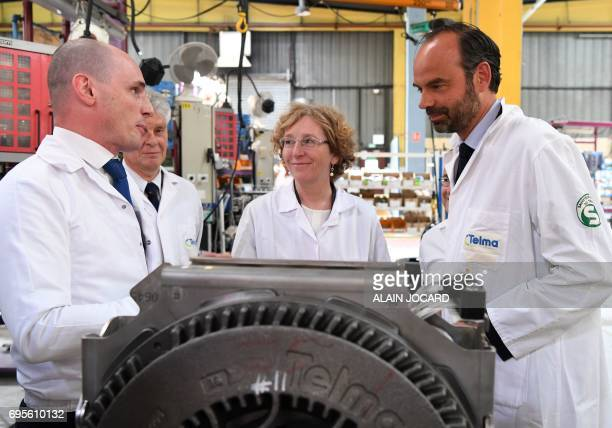 French Prime Minister Edouard Philippe and Minister of Labour Muriel Penicaud listen on during their visits to the Telma plant that manufactures...