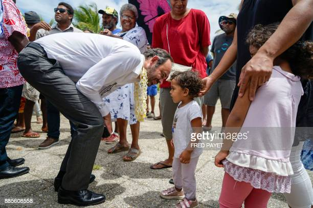French Prime Minister Edouard Philippe bends down to greet a small girl in the town of We in the Loyalty Islands Province of Lifou Island on December...