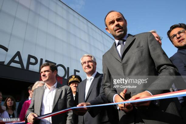 French Prime Minister Edouard Philippe cuts the ribbon next to ChalonsenChampagne mayor Benoist Apparu and Grand Est regional council president...